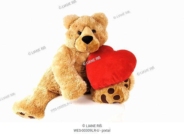 Reddy bear holding heart-shaped cushion