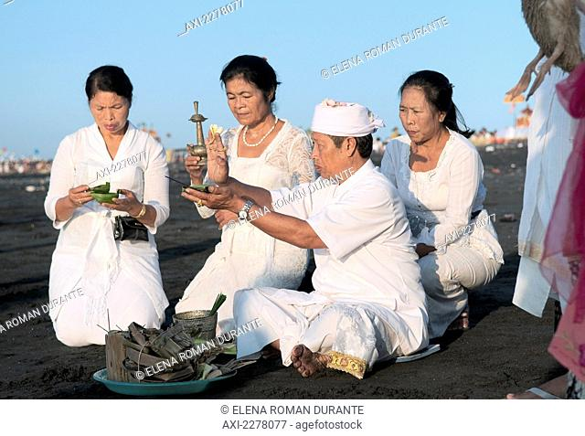 Family and priest making an offering at the Melasti Festival to honor the gods of the sea; Bali, Indonesia