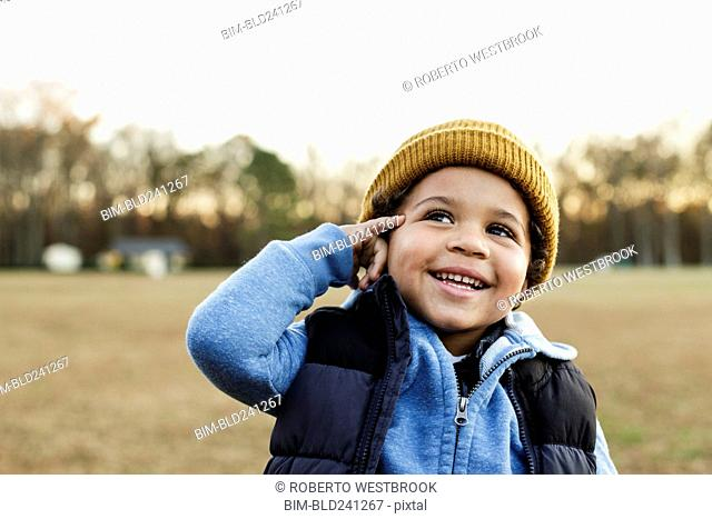 Mixed Race boy gesturing telephone in park