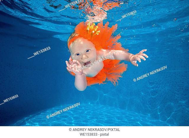 A little girl dressed as a princess under water in a pool