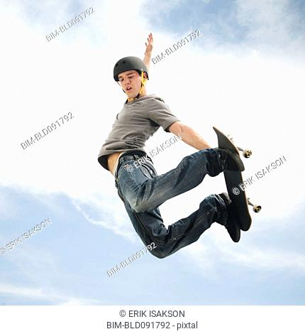 Caucasian man on skateboard in mid-air