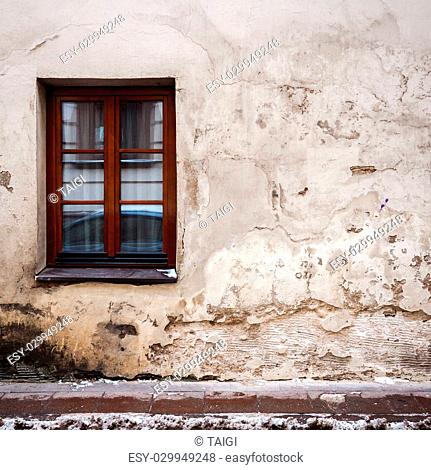Aged weathered street wall with a window