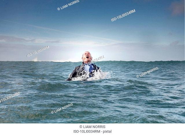 A businessman coming out of the sea