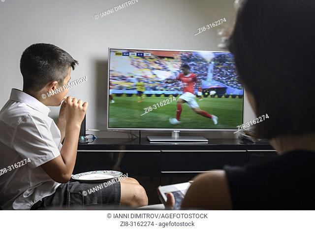 UK, London-Boy, 11 years old snacking and watching football match on TV