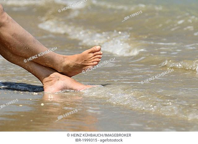Sea water flowing around the feet of a woman, Roseto degli Abruzzi, Abruzzo region, Italy, Europe