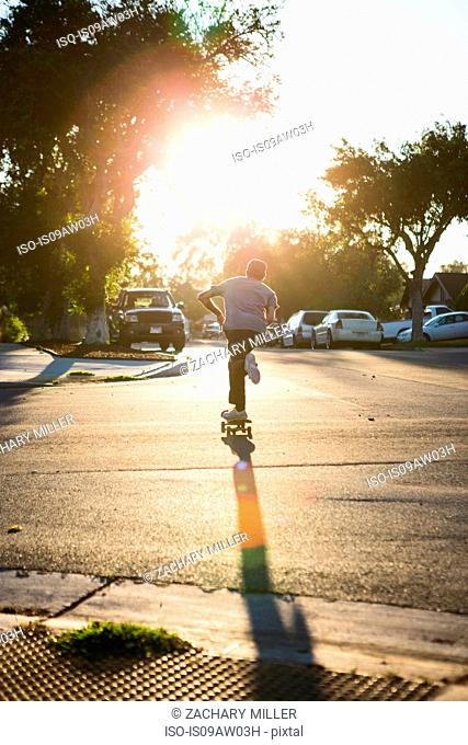 Young man skateboarding in road, rear view, Corona, California, USA