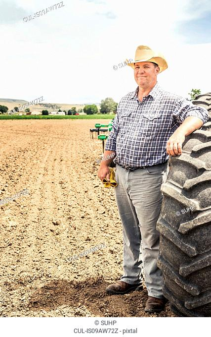 Portrait of male farmer leaning against tractor tyre in ploughed field