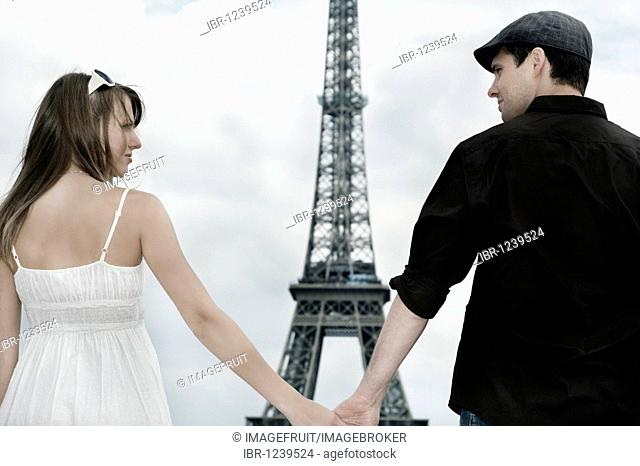 Young couple holding hands in front of the Eiffel Tower, Paris, France, Europe
