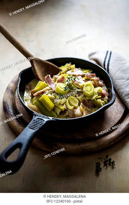 Creamy leeks with bacon in a small cast iron frying pan