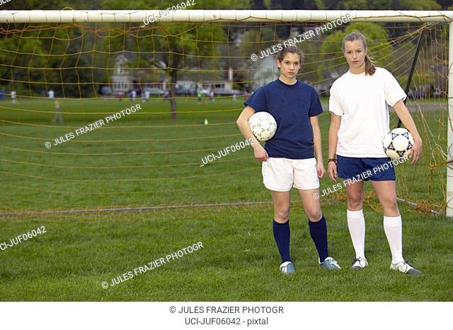 Teenage girls holding soccer balls
