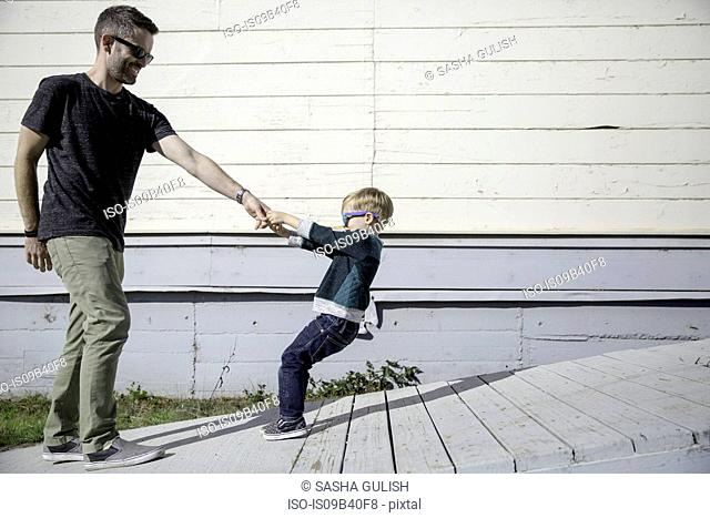 Boy pulling father up wooden ramp