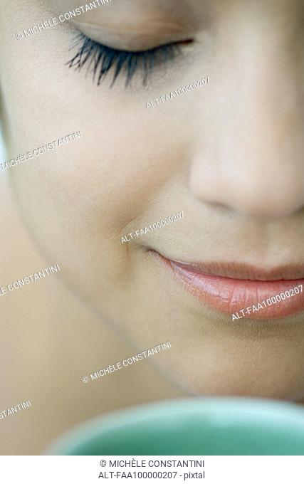 Woman smelling hot drink, eyes closed