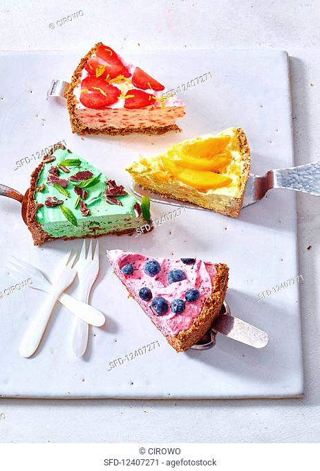 Pieces of different flavoured ice cream cakes on cake lifters