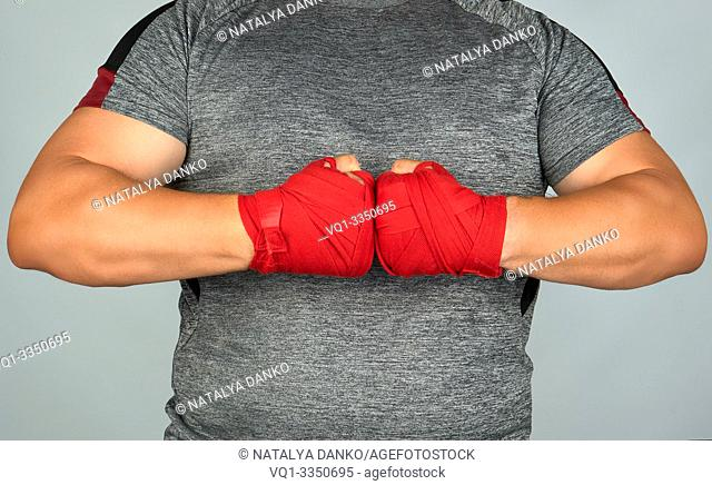 athlete in gray clothes joined his hands in front of his chest, two hands wrapped in a red textile sports bandage, white background