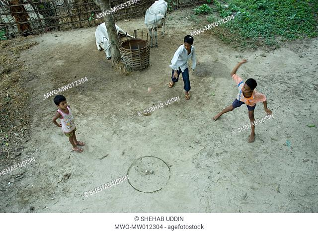 Children playing with tops, a traditional game in Bangladesh, in the village of Meherpur Bangladesh June 28, 2007