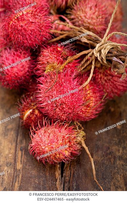 fresh tropical rambutan fruits over rustic wood table