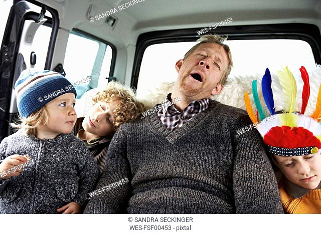 Sleeping father sitting in car on back seat with his sons