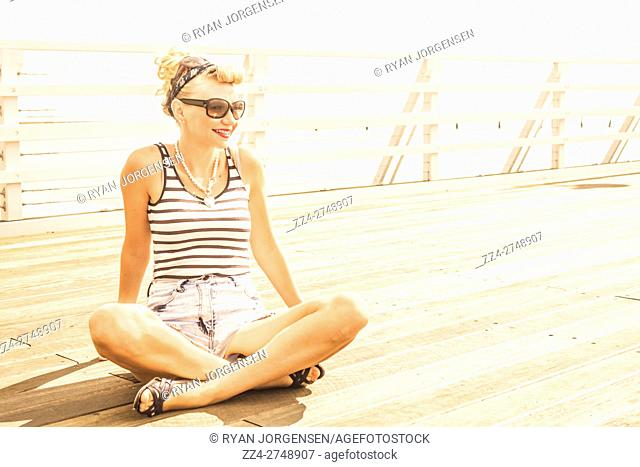 Antique old horizontal photo of a pretty pier girl wearing sailor stripes on wooden nautical riverside. Cross-legged beauty