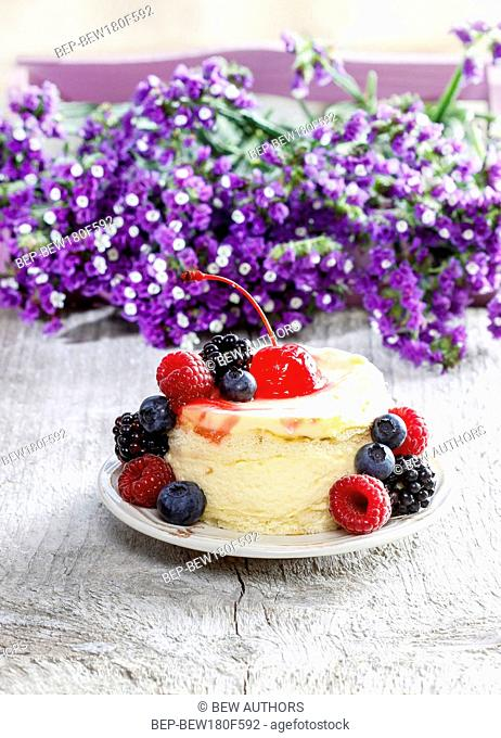 Round cake with fresh fruits. Purple flowers in the background. Selective focus