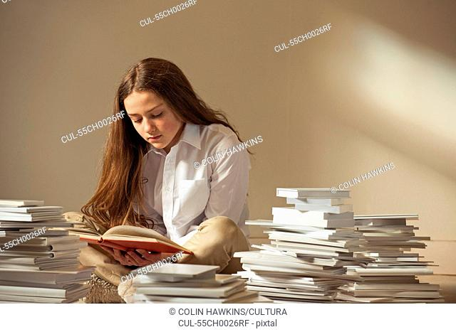 Girl sitting on floor reading surrounded by piles of books