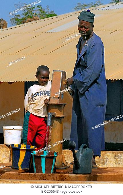 Father and son pumping water, Tumami Tenda, The Gambia, Africa