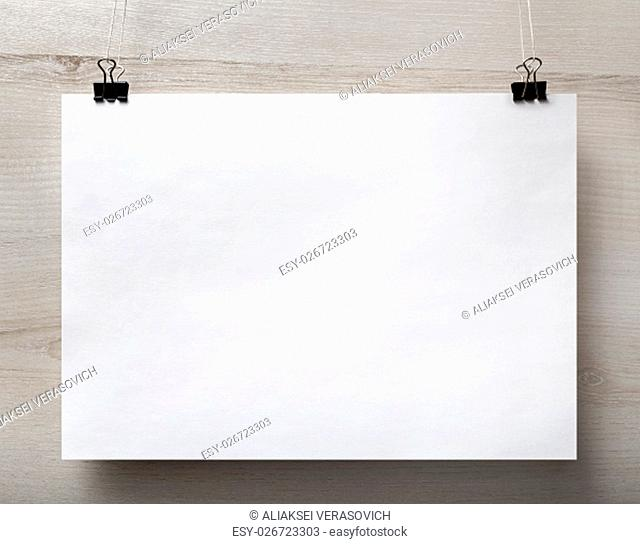 Blank white paper poster hanging on light wooden background. For design presentations and portfolios. Front view
