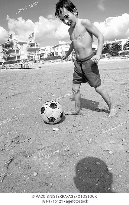 Boy playing soccer on the beach