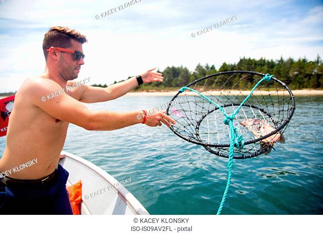 Mid adult man throwing baited crab trap from fishing boat, Nehalem Bay, Oregon, USA