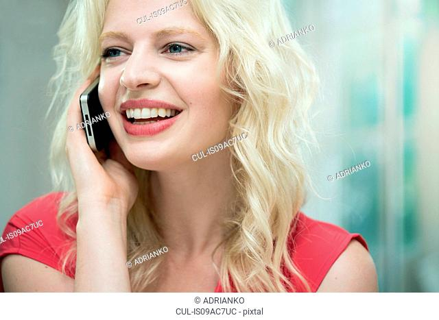 Young woman on cellphone, smiling