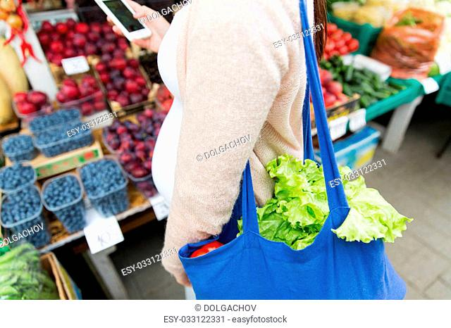 sale, shopping, food, pregnancy and people concept - close up of pregnant woman with smartphone and shopper bag at street market