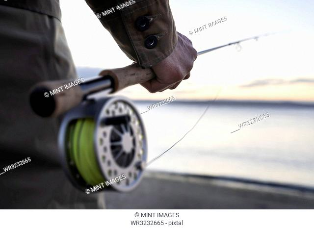 A closeup of a male hand holding a fly fishing rod and reel at the water's edge on a beach