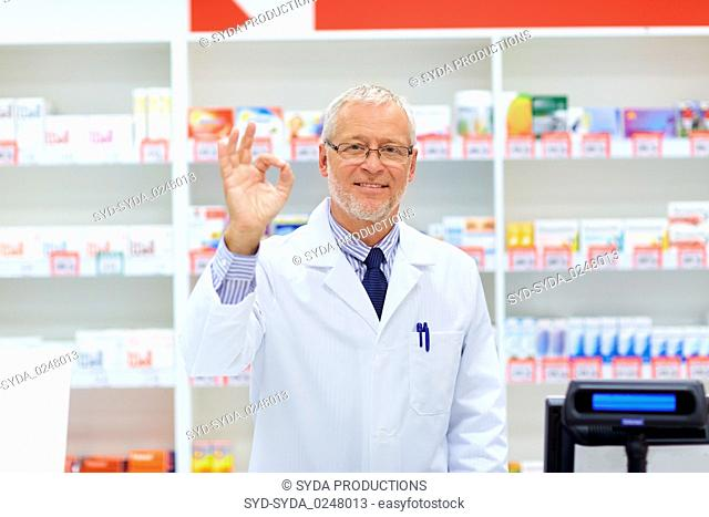 senior apothecary at pharmacy showing ok hand sign