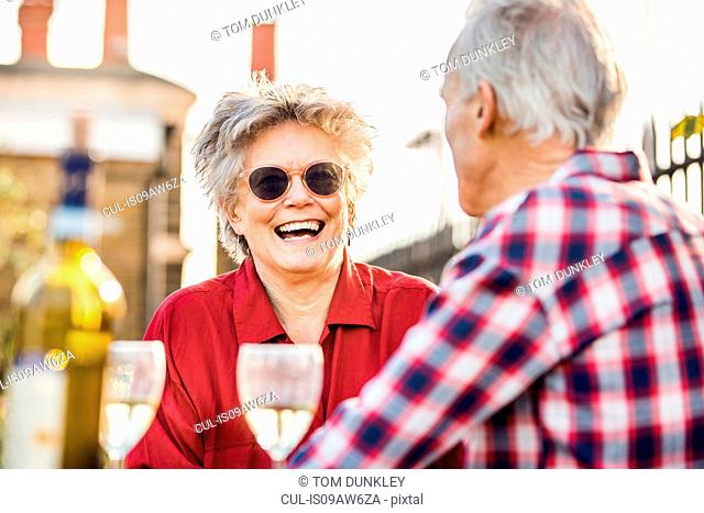Senior couple on city rooftop garden chatting and relaxing with white wine