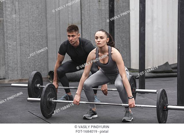 Full length of male and female athlete exercising with barbells during crossfit training