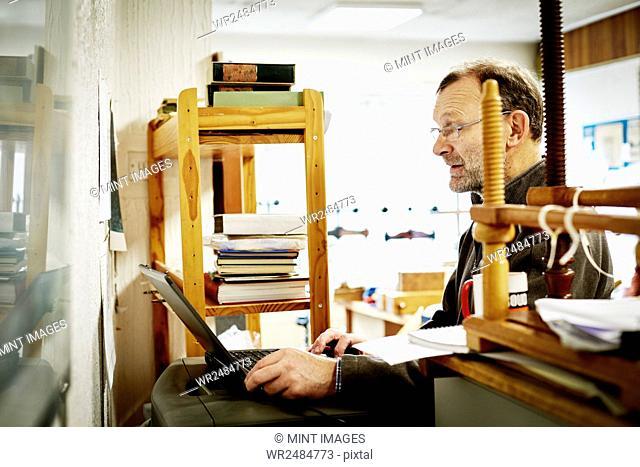A man using a laptop computer on a bookbinding business