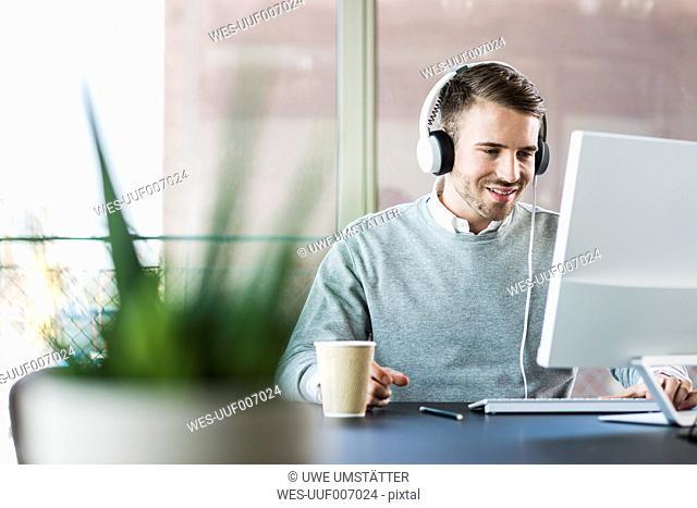 Man at office desk wearing headphones