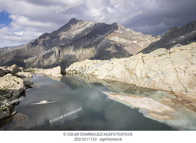 Small icy lake with Espadas peak in the background. Posets-Maladeta Natural Park. Aragon. Spain