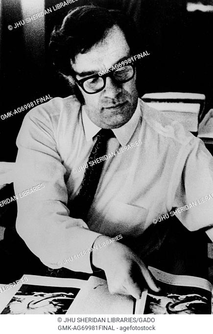 Half-length portrait of author Isaac Asimov, wearing a white shirt, sitting over a table, flipping through pages of a book, wearing glasses and a patterned tie