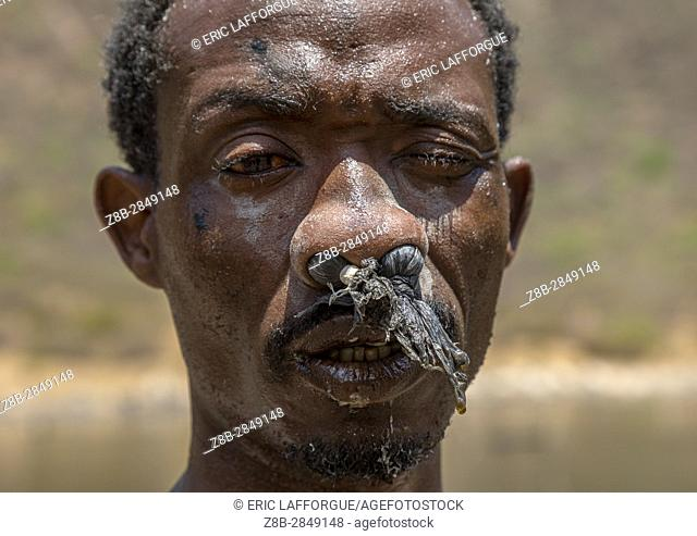 Borana tribe man with protection in his nose ready to dive in the volcano crater to collect salt, Oromia, El Sod, Ethiopia