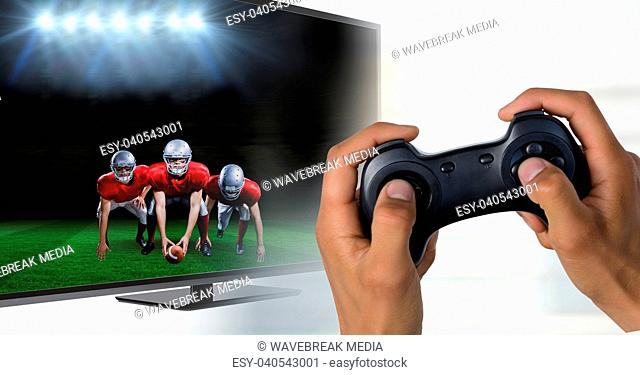 Hands with game controller in front of tv screen with goalkeeper reaching out the ball