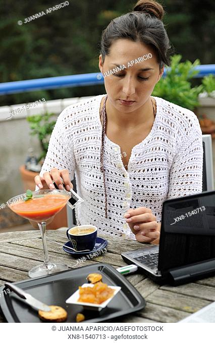 Young woman having breakfast on a terrace