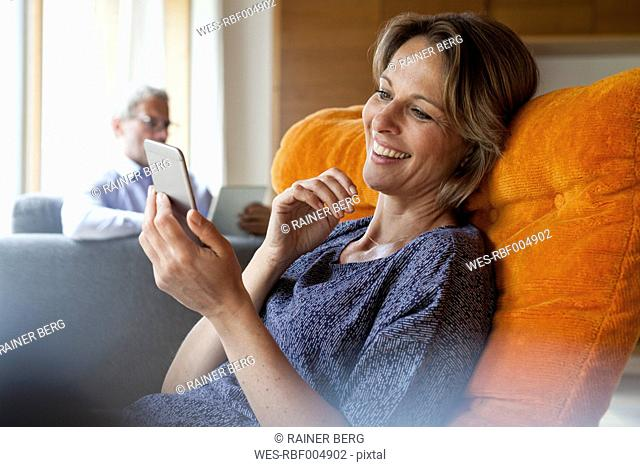 Smiling woman at home looking at cell phone with husband in background
