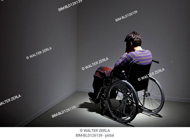 Frustrated Caucasian man in wheelchair in corner