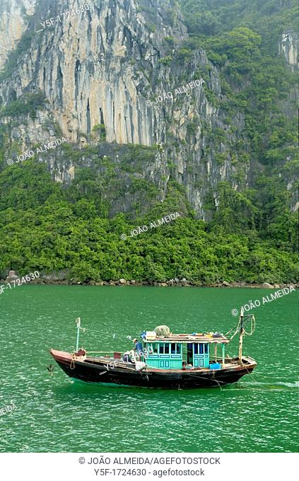 Small fishing boat at the cliffs of Halong