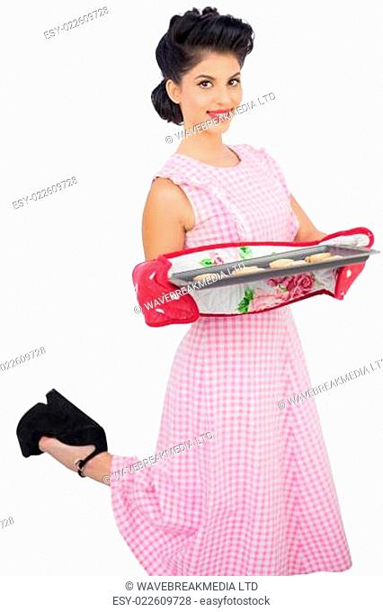 Content black hair model holding baking tray of cookies