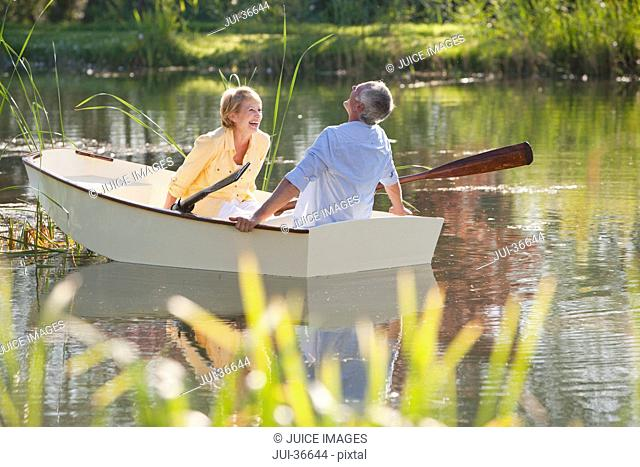 Senior couple laughing in rowboat on sunny lake