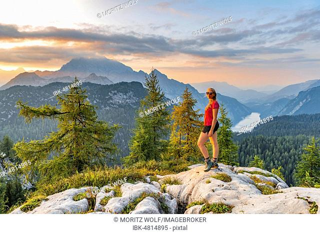 Hiker looks into the camera, view over the Königssee from the Feldkogel, left Watzmann Südspitze and Watzmann-Kinder, right Funtenseetauern, sunset