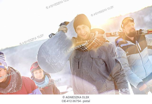 Portrait smiling snowboarder friends carrying snowboards