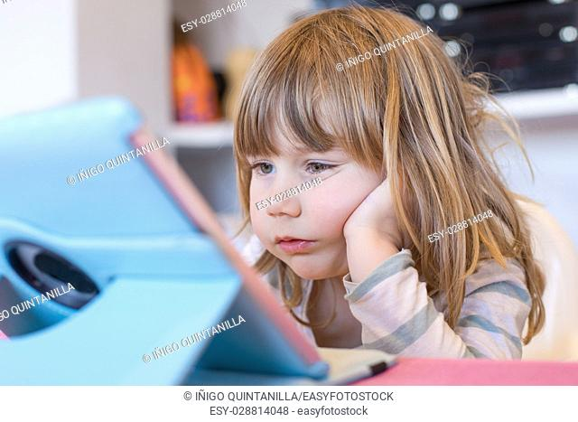 three years old blonde child sitting indoor, with head over hand watching digital tablet on table