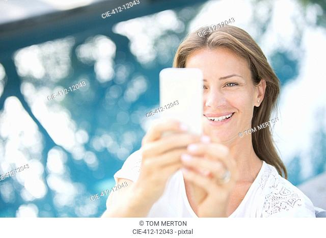Woman holding cell phone at poolside